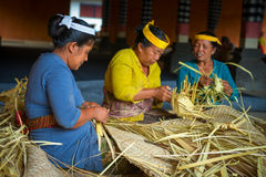 Balinese women make baskets for offerings Royalty Free Stock Images