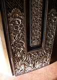 Balinese wood door details. Detail photograph of an old hand crafted wooden balinese door carved in the traditional intricate and ornate style of Bali.  Taken in Royalty Free Stock Images