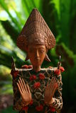 Balinese Wood & Old Asian Coin Statue. Coin cash china Bali antique retro collectable string tied Kepeng Bronze carved Traditional anthropomorphic Stock Image