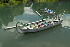 Balinese wooden boat with a one-sided counterweight, white, tied with a rope to the shore, in the background is another boat, refl Stock Photography