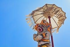 Balineseaffe Hanuman unter zeremoniellem Regenschirm Stockbilder