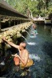 Balinesefolk som ber på heligt vårvatten på Pura Tirtha Empul Arkivbild