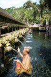 Balinesefolk som ber på heligt vårvatten på Pura Tirtha Empul Royaltyfri Foto