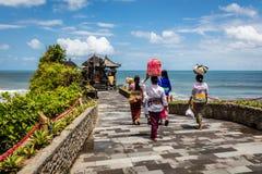 Balinesefrauen, die Körbe mit Angeboten zu einem Tempel bei Pura Tanah Lot, Bali-Insel, Indonesien tragen Lizenzfreies Stockbild