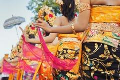 Balinesekvinnor i ljusa dräkter med traditionella garneringar Royaltyfria Bilder