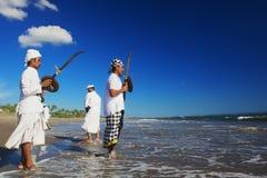 Balinesemän med rituella svärd på havskusten Arkivfoto