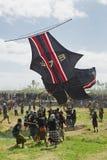 Balinesemänner versuchen, großen traditionellen Drachen zu fangen Stockbild