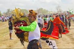 Balinesemann, der Drachen mit Drachekopf und -langem Schwanz hält Stockbild