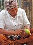 Balinesemann, welche einer Mango abzieht stockbilder