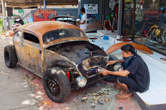 Balinesemannen förnyar den gamla bilen Arkivfoto