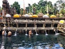 Balinesen renar sig, genom att bada på Pura Tirta Empul ett komplex för hinduisk tempel royaltyfria bilder