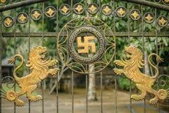 Balinesetempelport med Swastica och två lejon Arkivbilder