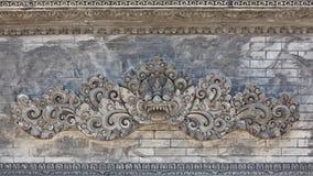 Balinesetempelvägg med det traditionella vaktdemonhuvudet Arkivbilder