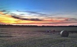 Baling Hay at Sunset. Tractor and round baler baling round bales of hay in a hay field at sunset Royalty Free Stock Photos