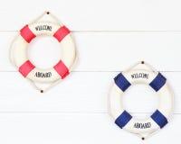Balise de vie blanche avec l'accueil à bord sur le mur blanc Photographie stock