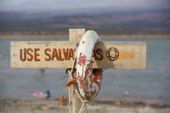 Balise et signe de vie dangereux pour nager, lac de vent, Argentine Photographie stock