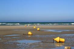 Balises jaunes sur la plage à marée basse Photo stock