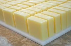 Bulk Batch Handmade Soap Bars. Bulk batch of yellow handmade soap cut into bars freshly made in the soap shop royalty free stock images