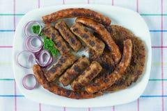 Balkan cuisine. Cevapi, kobasica and pljeskavica - grilled dish of minced meat. Flat lay. Balkan cuisine. Cevapi, kobasica and pljeskavica - grilled dish of stock images