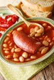 Balkan food pasulj soup with sausage served with pickled pepper stock photo
