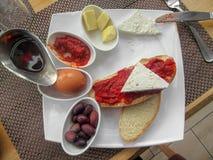 Balkan frukost - bröd, vit ost, chutney, ägg, smör, oliv och att sörja honung arkivbild