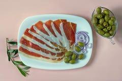 Balkan keuken De witte plaat met plakken van prsut droog-genezen ham, prosciutto op roze pastelkleurachtergrond, vlakte lag royalty-vrije stock fotografie