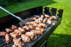 Balkan meatballs called cevapi on barbecue with BBQ fork Stock Photography