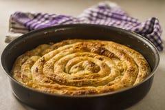 Balkan-Torte Burek frisch aus dem Ofen in rundem Pan heraus lizenzfreies stockfoto