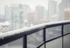 Balkon, der mit Schnee, Stadthintergrund raling ist Lizenzfreies Stockbild