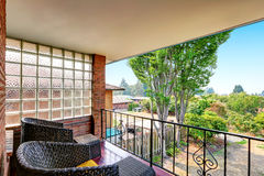 Balkon met smeedijzertraliewerk en zwarte rieten stoelen Royalty-vrije Stock Afbeelding
