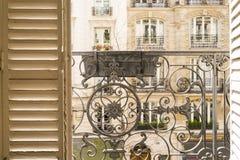 Balkon mit dekorativem Geländer und Fensterläden in Paris, Frankreich lizenzfreies stockbild