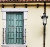 Balkon z zielonymi drzwiami i klasyczny lamppost na żółtej fasadzie Zdjęcia Stock