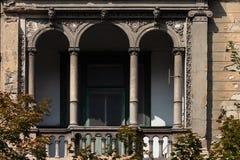 Balkong med dekorativa bågar på en gammal byggnad royaltyfri bild