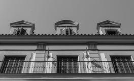Balkong och fönster med portar av det gamla centrumhuset i Sevil royaltyfria foton