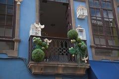 Balkong som dekoreras med fågelburar och duvor Arkivbilder