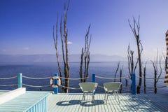 Balkongen med havssikter och två stolar semestrar Fotografering för Bildbyråer