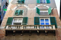 Balkonger och fönster med gräsplan splittrar på fasad av byggnad i Genova, Italien arkivbilder