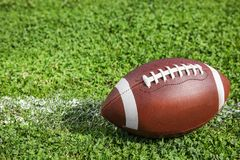 Ball for American football on fresh green field grass royalty free stock images