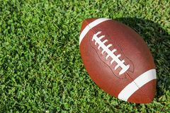 Ball for American football on fresh green field grass. Space for text stock photo