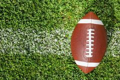 Ball for American football on fresh green field grass. Top view. Space for text royalty free stock photos