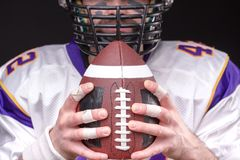 Ball for American football in front of footballer face. Close up portrait stock photo