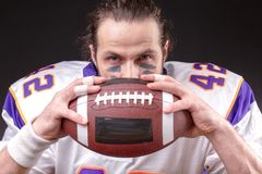 Ball for American football in front of footballer face. Close up portrait royalty free stock photo