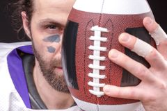 Ball for American football in front of footballer face. Close up portrait royalty free stock images