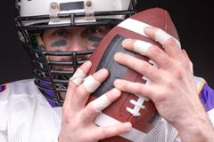 Ball for American football in front of footballer face. Close up portrait stock image