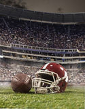 The ball of american football players and helmet on stadium background. The ball of american football players with helmet on stadium background Royalty Free Stock Images