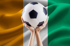 Ball on the arms with flag of Ivory Coast Royalty Free Stock Images