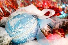 Ball auf den schneebedeckten Niederlassungen eines Weihnachtsbaums gegen einen Hintergrund des glänzenden Lamettas Lizenzfreies Stockfoto