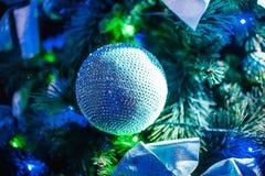 Ball auf Weihnachtskünstlichen Baumniederlassungen auf Niederlassungsnahaufnahme mit bunten Lichtern und unscharfem Hintergrund Lizenzfreies Stockfoto