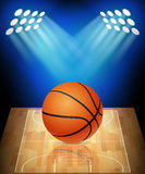 Ball on basketball court with spotlights Stock Images