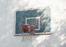 Ball basketball going through rustic old hoop with backboard Stock Photo